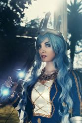 1girl ashe_(league_of_legends) ashe_(league_of_legends)_(cosplay) bangs blue_eyes blue_hair bow cosplay crown ice league_of_legends long_hair looking_at_viewer makeup nail_polish outdoors photo queen solo tree valentina_kryp weapon
