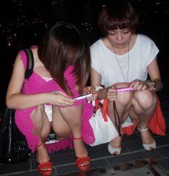 2girls cellphone japanese multiple_girls panties pantyshot photo squatting underwear upskirt