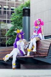 2girls boots cosplay elf english feli_dragoon high_heel_boots high_heels janna_windforce league_of_legends long_hair looking_at_viewer luxanna_crownguard multiple_girls outdoor pink_hair purple_hair sitting skirt star twintails valentina_kryp wig