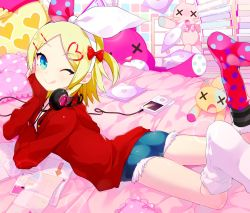 1girl :q akemaru aqua_eyes ass bed blonde_hair blush cd_case chin_rest commentary_request denim denim_shorts digital_media_player hair_ornament hair_ribbon hairclip headphones headphones_around_neck hood hoodie kagamine_rin looking_at_viewer lying on_stomach one_eye_closed pillow ribbon short_hair short_twintails shorts smile solo tongue tongue_out twintails vocaloid