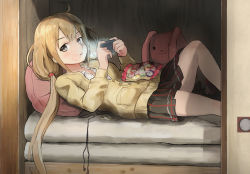 1girl ahoge black_eyes black_skirt buttons candy candy_wrapper chewing commentary_request earbuds earphones futaba_anzu handheld_game_console holding idolmaster idolmaster_cinderella_girls kamemaru light long_hair long_sleeves long_twintails looking_at_viewer low_twintails lying on_back on_bed pillow playstation_portable pleated_skirt skirt solo stuffed_animal stuffed_bunny stuffed_toy sweater twintails wrapper zashiki-warashi