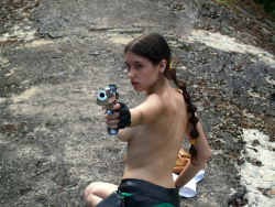 1girl braid breasts cosplay gloves gun lara_croft looking_back photo tomb_raider topless weapon