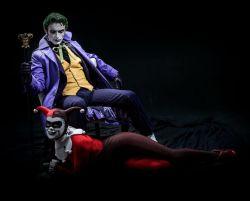 1boy 1girl alyssa_king anthony_misiano batman_(series) bodysuit chair cosplay dc_comics domino_mask gloves harley_quinn hat jacket jester_cap joker on_stomach photo pinstripe_pattern sitting smile staff suit the_joker waistcoat