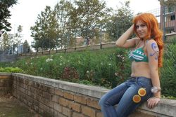 1girl bikini bikini_top breasts cosplay jeans large_breasts nami nami_(cosplay) one_piece orange_hair photo sitting solo wall