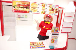 1girl asian bowtie brand_name_imitation breasts brown_eyes brown_hair chouzuki_maryou cosplay employee_uniform fast_food fast_food_uniform female food hamburger hataraku_maou-sama! large_breasts photo plump polo_shirt ribbon sasaki_chiho sasaki_chiho_(cosplay) short_hair short_twintails skirt solo twintails uniform visor_cap