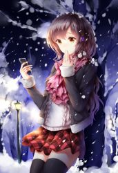 1girl against_tree black_legwear black_sweater brown_hair cellphone covering_mouth eyebrows_visible_through_hair hand_over_own_mouth highres holding holding_phone long_hair looking_at_phone night original outdoors phone pleated_skirt red_skirt skirt smartphone snow snowing solo sweater thighhighs tree wsman yellow_eyes zettai_ryouiki