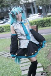 1girl cosplay female green_eyes green_hair hatsune_miku long_hair nature outdoors photo plant skirt smile solo tie twintails vocaloid
