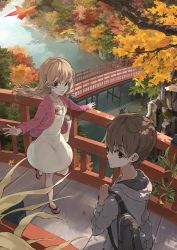 1boy 1girl autumn_leaves bag black_eyes bridge brown_hair casual dappled_sunlight dress falsehood from_above hair_ornament hood_down hoodie jacket long_hair long_sleeves looking_back open_clothes open_jacket open_mouth original outdoors railing reflection river scenery short_hair shoulder_bag standing_on_one_leg tree tree_branch water