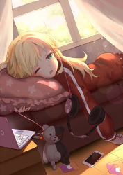 1girl aliter apple_inc. blonde_hair blue_eyes blush cellphone computer couch curtains danganronpa dutch_angle eyebrows_visible_through_hair frilled_pillow frills gabriel_dropout headphones highres indoors jacket laptop lens_flare long_hair long_sleeves lying monokuma on_stomach one_eye_closed open_mouth phone pillow smartphone star star_print sunlight tenma_gabriel_white tile_floor tiles track_jacket window